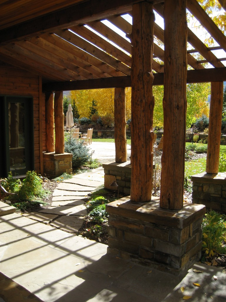 Logs and sloped pergola create a cozy entry.